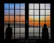 Silhouette of a young couple standing and looking through big window at beautiful foggy hills with coloful sunset. 117308491