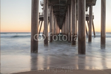 Under the Huntington Beach, California pier at sunset in the fall 95775583