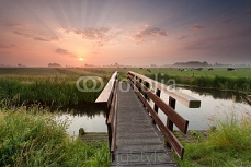 beautiful sunrise over bike bridge in farmland 89098149