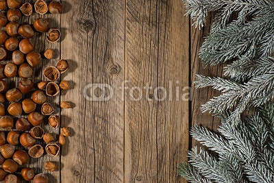 Hazelnuts and a branch of spruce in the snow on an old wooden ta 127903529