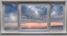 A window with the panoramic views of the sea and the beautiful sunrise 111142016